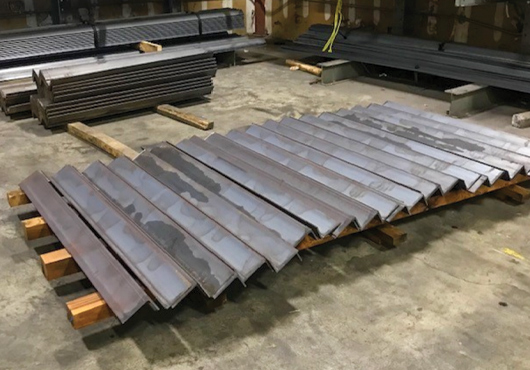 Hudson Valley Windustrial Co. Metal Supply provides fabricated angle cut to size for a large NYC-based job, which is pictured here alongside stock material lining the walls of the company's warehouse.