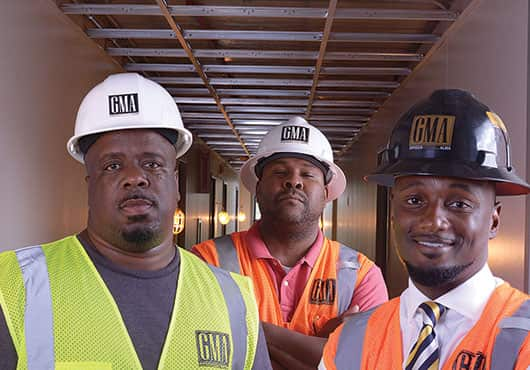 GMA Construction Group hires people like Carl Nesbitt, Assistant Superintendent (pictured on the left) from within the housing communities it renovates.  Also shown are Deon King, Superintendent (middle)  and Cornelius Griggs, President.