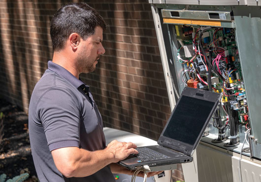 Service professional Sean Rusnak performs diagnostics on a VRF system.  All Westland Heating & Air Conditioning technicians are trained on start-up  procedures and the precise calculations required on these highly efficient systems.